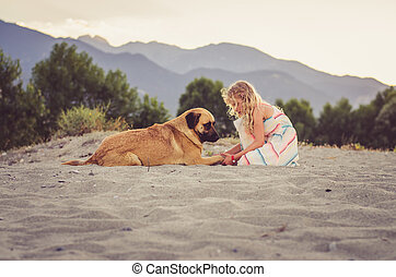 happy kid and dog in the sandy beach