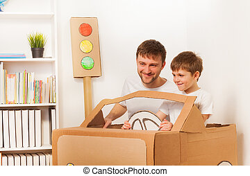 Happy kid and his dad driving toy cardboard car
