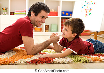 Happy kid and his father arm wrestling - Happy boy and his...