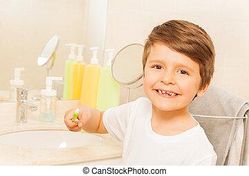 Happy kid boy brushing teeth in the bathroom
