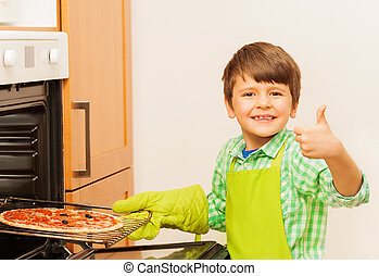 Happy kid boy cooking homemade pizza in the oven