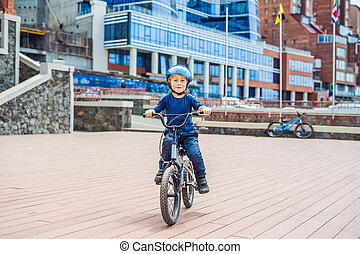 Happy kid boy having fun near the yacht club with a bicycle on beautiful day. Active child wearing bike helmet