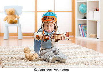 Happy kid boy playing with toy airplane at home in his room