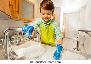 Happy kid boy rinsing dishes in the sink