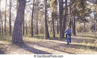 Happy kid cyclist rides in the forest on a mountain bike. - ...