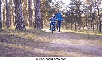 Happy kid cyclist with his mom rides in the forest on a ...