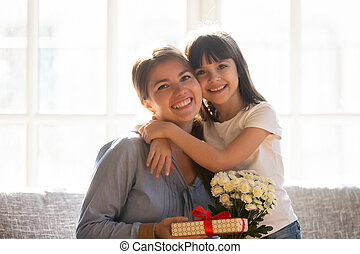 Happy kid daughter embracing mom holding flowers bouquet and gift
