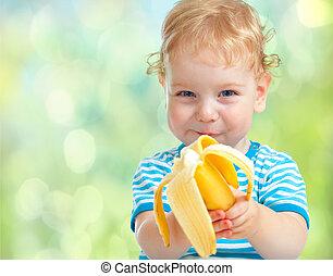 happy kid eating banana fruit. healthy food eating concept.