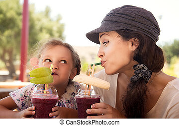 Happy kid girl and funny emotional mother drinking berries...