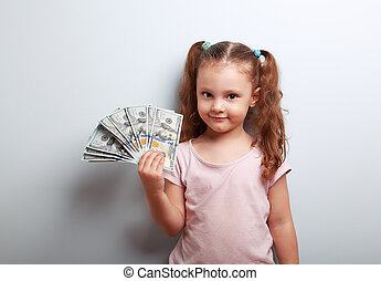 Happy kid girl holding many dollars in the hand and smiling