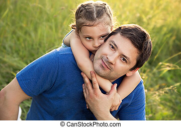 Happy kid girl hugging with love her smiling father on summer green grass background. Closeup portrait