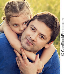Happy kid girl hugging with love her smiling father on summer green grass background. Closeup portrait of love