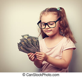 Happy kid girl in glasses looking and counting the money. Vintage portrait