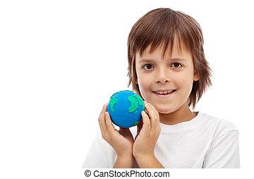 Happy kid holding earth globe made of clay