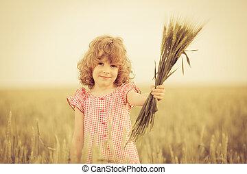 Happy kid holding wheat