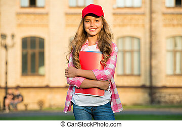 Happy kid in casual fashion style hold school books outdoors, private teaching.
