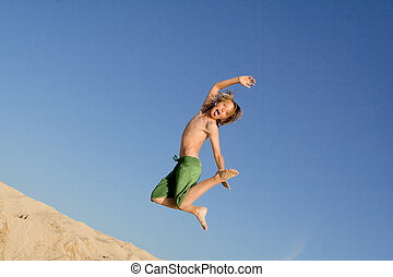 happy kid jumping on beach in summer vacation or holiday