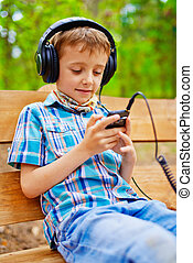 Happy kid listening to music on stereo headphones