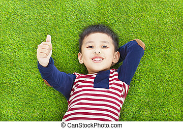 happy kid lying and raise his thumb on a meadow