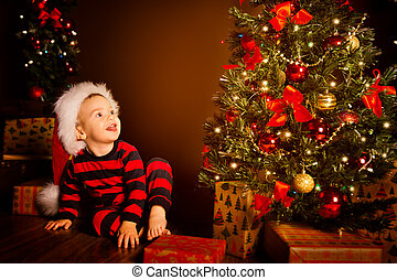Happy Kid near Christmas Tree, Happy Baby Boy in Night Xmas Room, Child in Red Santa Hat with Present gift box