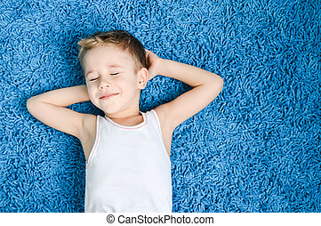 Happy kid on floor in living room - Happy boy smiling kid on...