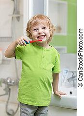 Happy kid or child brushing his teeth in bathroom. Dental hygiene.