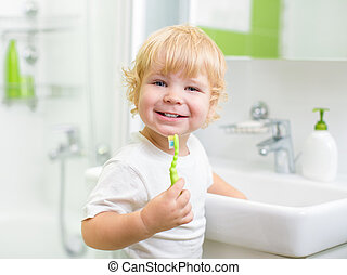 Happy kid or child brushing teeth in bathroom. Dental...