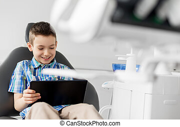 happy kid patient with tablet pc at dental clinic