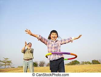 happy kid playing  hula hoops outdoors