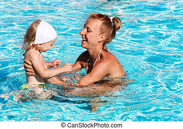 Happy kid playing with mother in swimming pool