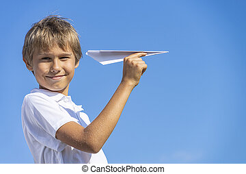 Happy kid playing with paper airplane against blue summer sky background