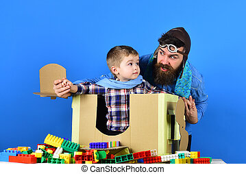 Happy kid playing with toy airplane on blue background. Developing funny games with toddler. Boy wearing blue scarf sits in small cardboard plane. Family leisure at home. Father and son together