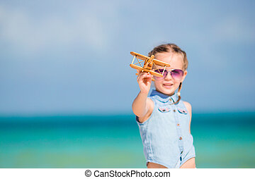 Happy kid playing with toy airplane on the beach.