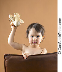 Happy kid playing with toy airplane. Studio shot.