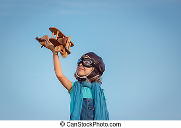 Happy kid playing with wooden toy airplane