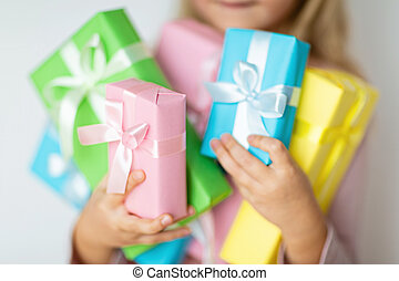 Happy kid receiving present on boxing day. Little girl smiling with wrapped present box. Small child in pink hat holding birthday gift isolated on white background. Holiday, celebration concept