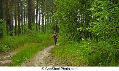 Happy kid running along the road in a summer forest