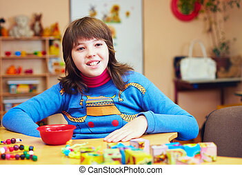 happy kid with disability develops fine motor skills at...