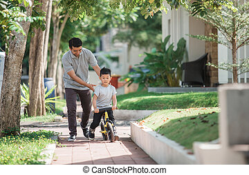 kid with his father learning how to ride a bicycle