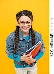 Happy kid with nerd look hold school books in casual fashion style yellow background, back to school.