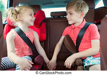 Happy kids, adorable girl with her brother sitting together in modern car locked with safety belts enjoying family vacation trip