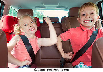 Happy kids, adorable girl with her brother sitting together...