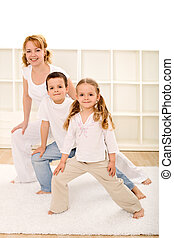 Happy kids and woman doing gym exercises