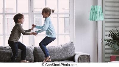 Happy kids boy and girl having fun jumping on sofa