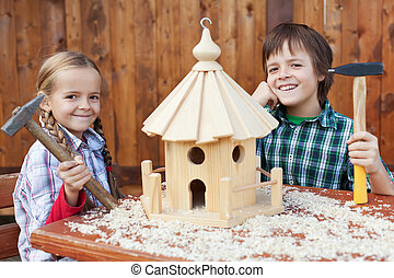 Happy kids building a bird house - smiling and holding hammers