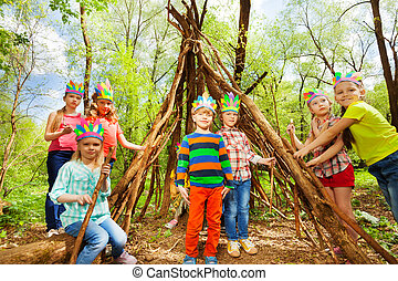 Happy kids building Injun's wigwam in the forest