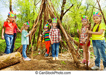Happy kids building wigwam in the forest