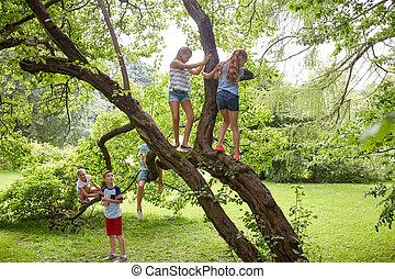 happy kids climbing up tree in summer park - friendship, ...