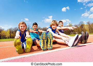 Happy kids doing stretching exercises on a stadium -...