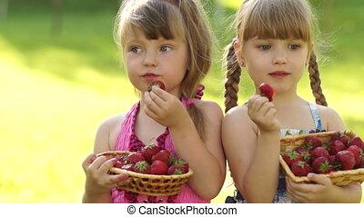 Happy kids eat strawberries